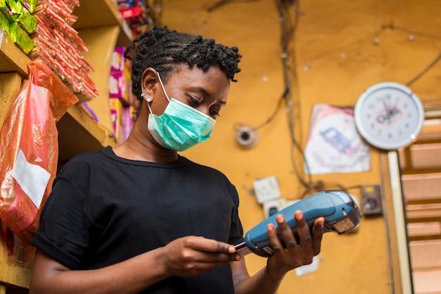 Młoda afrykańska asystentka za pomocą automatu w punkcie sprzedaży, aby zapłacić za towary kupione przez jej klienta, używając maski na twarz, aby zapobiec wybuchowi korony.