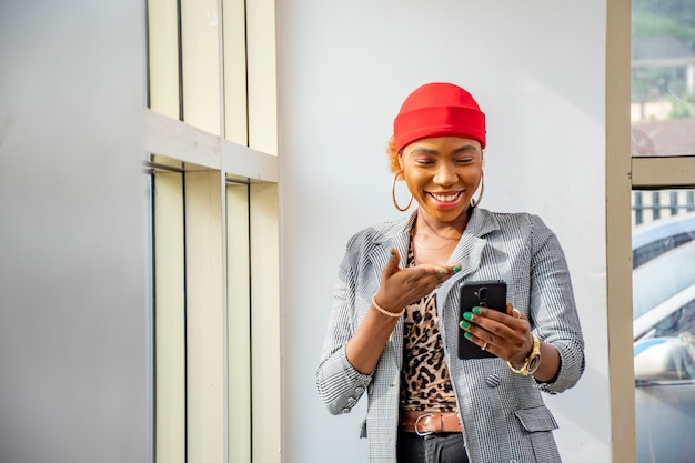 Młoda afrykańska bizneswoman czuje się podekscytowana i szczęśliwa, uśmiechając się trzymając swój telefon komórkowy