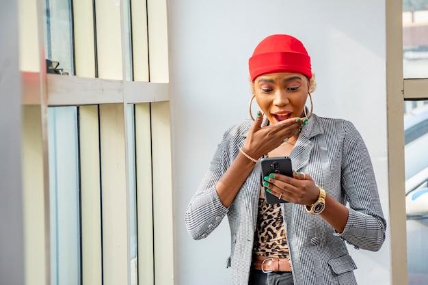 Młoda afrykańska bizneswoman czuje się podekscytowana i zaskoczona, patrząc na swój telefon komórkowy