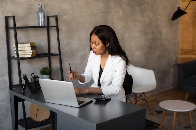 Młoda afrykańska bizneswoman nosi słuchawki uczą się online oglądając webinarium podcast na laptopie słuchanie nauka edukacja kurs rozmowy konferencyjne robienie notatek siedzieć przy biurku koncepcja elearning