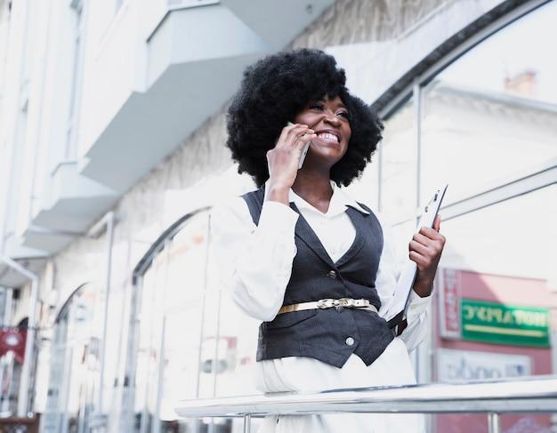 Młoda afrykańska bizneswoman pozycja na zewnątrz budynku opowiada na mądrze telefonie