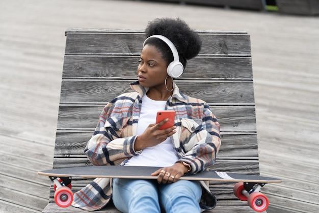 Młoda afrykańska deskorolkarz kobieta czat w smartfonie czarna łyżwiarka dziewczyna w przestrzeni miejskiej z telefonem komórkowym