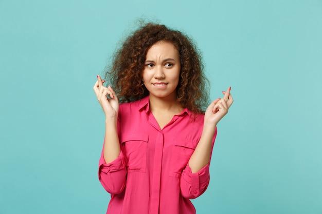 Młoda afrykańska dziewczyna czeka na wyjątkowy moment, trzymając kciuki, gryząc usta, życząc na białym tle na niebieskim turkusowym tle. ludzie szczere emocje, koncepcja stylu życia. makieta miejsca na kopię.