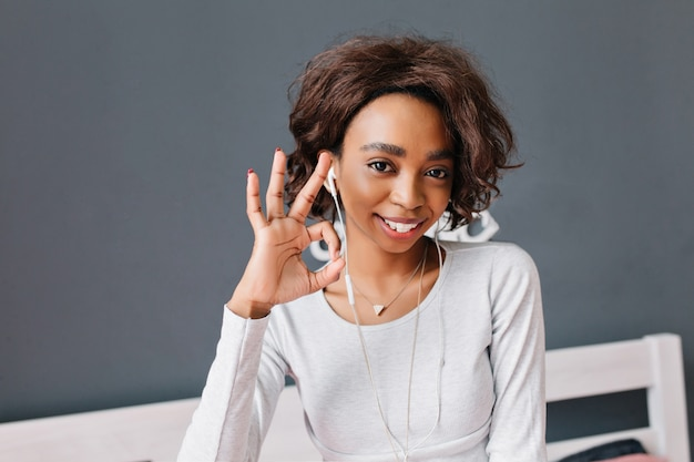 Młoda afrykańska dziewczyna uśmiecha się, pokazuje dobrze, słucha muzyki w słuchawkach, miło spędza czas w domu. szara ściana z białymi meblami. ubrana w jasnoszarą koszulkę z długimi rękawami.