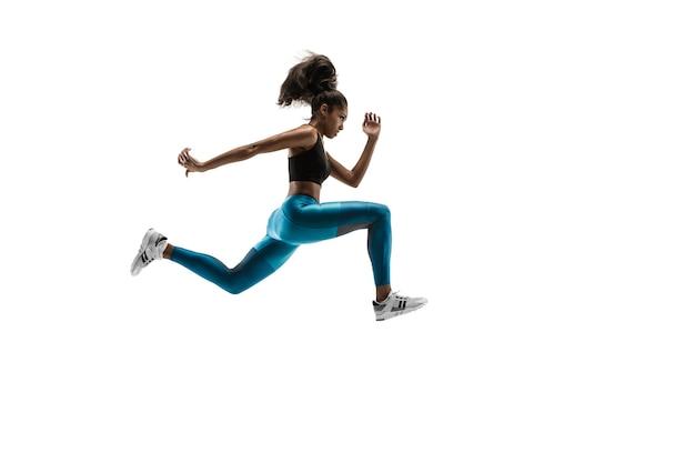 Młoda afrykańska kobieta działa na białym tle na tle białego studia. jedna biegaczka lub jogger. sylwetka sportowca joggingu