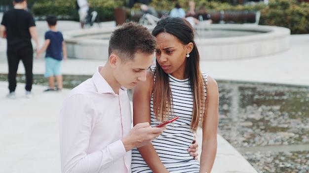 Młoda afrykańska kobieta jest zdenerwowana, ponieważ jej chłopak cały czas patrzy w smartfon