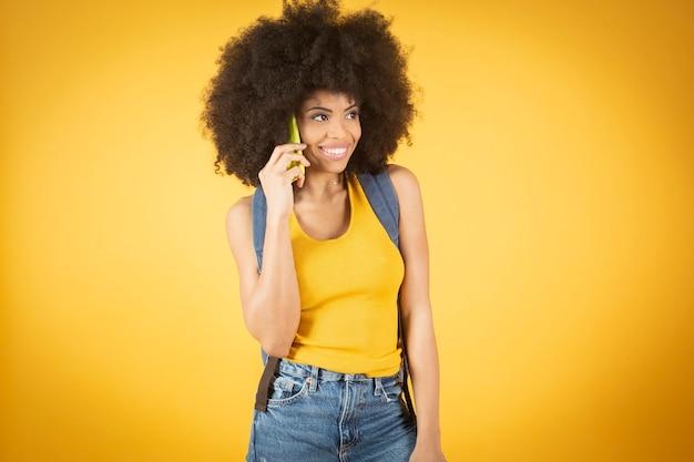Młoda afrykańska kobieta mieszana, rozmawia przez telefon, na żółtym tle, komunikacja mobilna