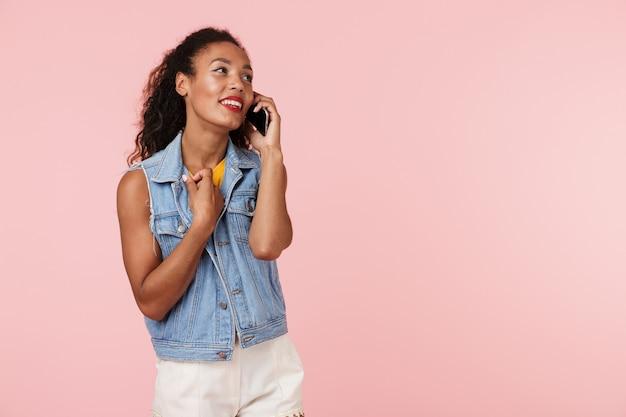 Młoda afrykańska kobieta na białym tle nad różową ścianą rozmawia przez telefon