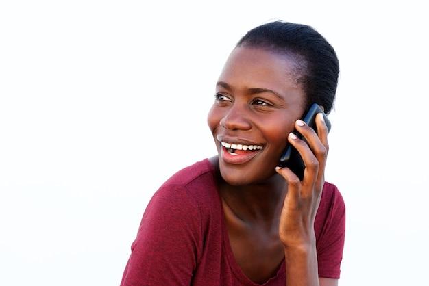 Młoda afrykańska kobieta robi rozmowie telefonicza patrzeje nad ramieniem i ono uśmiecha się na białym tle