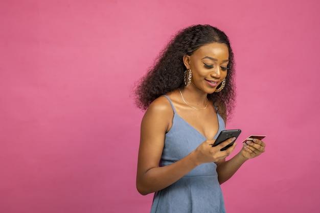 Młoda afrykańska kobieta robi zakupy online za pomocą swojego smartfona i karty kredytowej