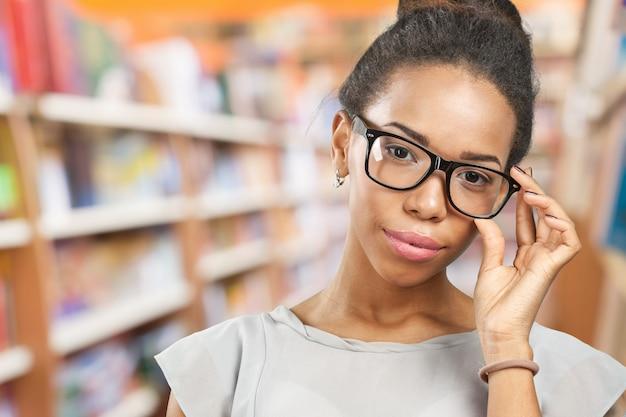 Młoda afrykańska kobieta trzyma jej eyeglasses