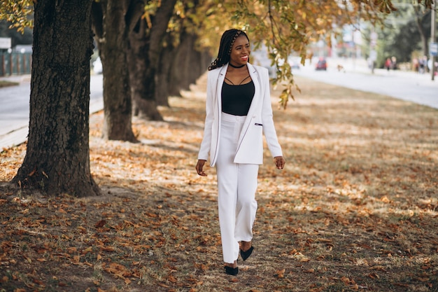 Młoda afrykańska kobieta ubierał w białym kostiumu w parku