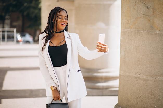Młoda afrykańska kobieta w białym kostiumu używać telefon