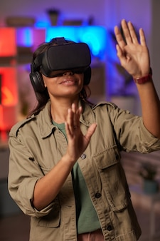 Młoda afrykańska kobieta w okularach gestykuluje stojąc w pokoju i grając w grę vr