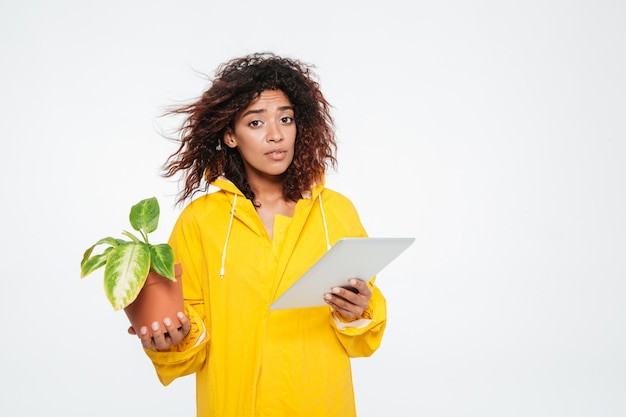 Młoda afrykańska kobieta w płaszczu mienia roślinie