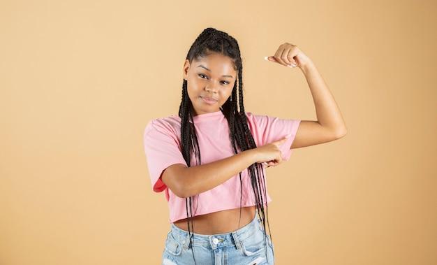 Młoda afrykańska kobieta wskazująca na biceps silną kobietę