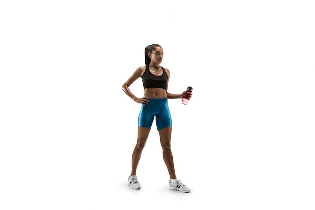 Młoda afrykańska kobieta z wodą przed uruchomieniem na białym tle na tle białego studia. jedna biegaczka lub jogger. sylwetka sportowca.