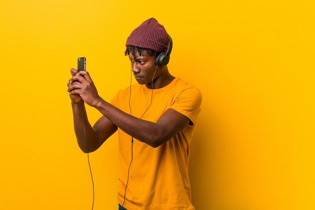 Młoda afrykańska mężczyzna pozycja jest ubranym kapelusz słucha muzyka z telefonem