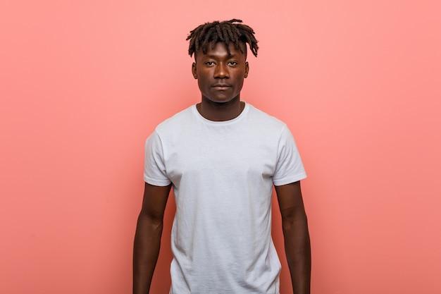 Młoda afrykańska mężczyzna pozycja przeciw menchii ścianie