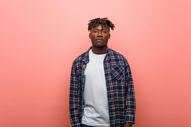 Młoda afrykańska mężczyzna pozycja przeciw różowemu tłu