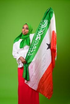 Młoda afrykańska muzułmańska kobieta przeciwko klucz chroma z zieloną ścianą
