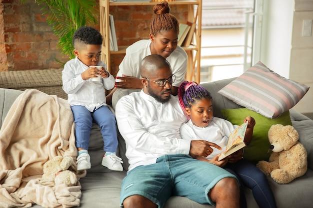 Młoda afrykańska rodzina podczas izolacji kwarantannowej spędzająca razem czas w domu
