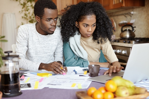 Młoda afrykańska rodzina składa się z dwóch osób zarządzających finansami w domu, przeglądających rachunki bankowe, siedzących przy kuchennym stole z komputerem przenośnym i kalkulatorem. żona i mąż płacą podatki online na laptopie