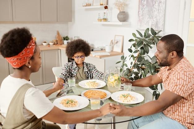 Młoda afrykańska trzyosobowa rodzina modli się przed obiadem z zamkniętymi oczami