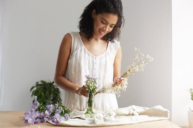 Młoda afrykańska żeńska kwiaciarnia ono uśmiecha się pracować z wiązką kwiaty przy miejscem pracy nad biel ścianą.