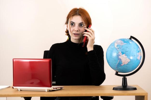 Młoda agent biura podróży kobieta siedzi za biurkiem rozmawia przez telefon komórkowy.