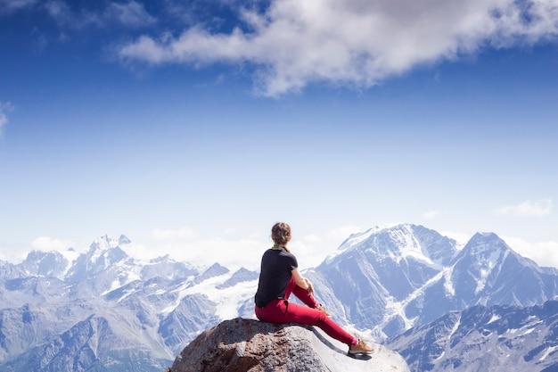 Młoda aktywna dziewczyna siedzi plecami na skraju urwiska na tle