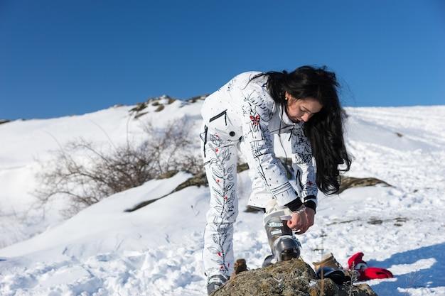 Młoda, aktywna kobieta pochyla się, aby dopasować swój sprzęt narciarski na śniegu.
