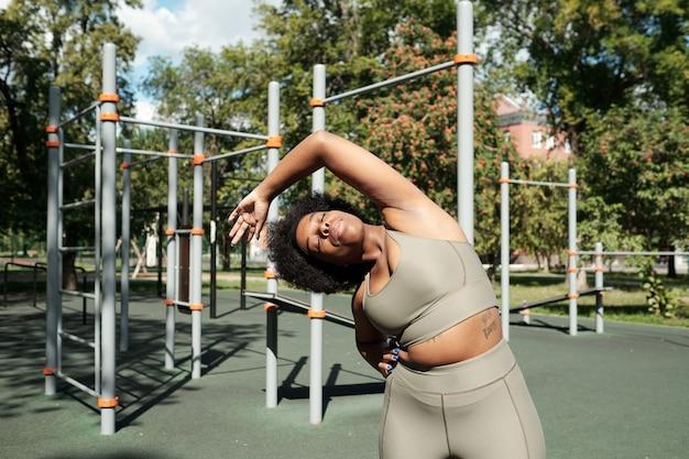Młoda aktywna kobieta robi skłony boczne w słoneczny poranek