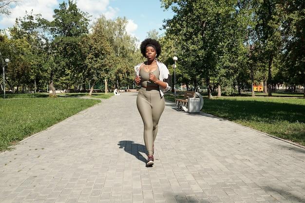 Młoda, aktywna kobieta w dużych rozmiarach, biegająca wzdłuż drogi