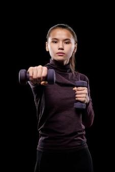 Młoda aktywna kobieta z hantlami wyciągając ramię do przodu podczas ćwiczeń