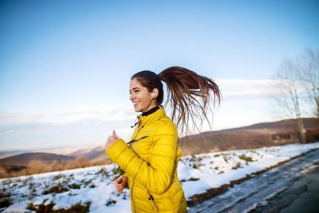 Młoda aktywna sportowa dziewczyna jogging w zimowej odzieży sportowej na zaśnieżonej zimowej drodze ze słuchawkami w słoneczny poranek.