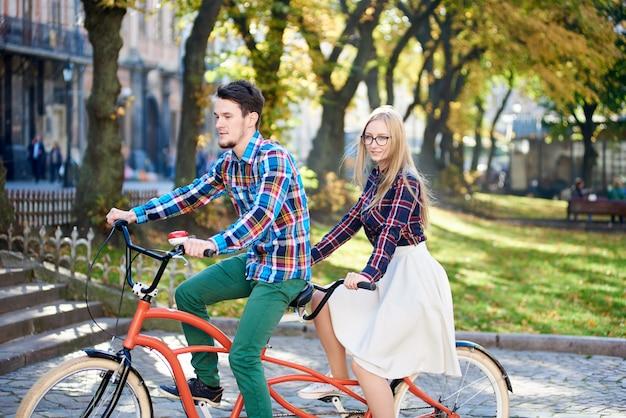 Młoda aktywna szczęśliwa podróżnik para, przystojny brodaty mężczyzna i ładna blond kobieta na tandemowym rowerze w jasny słoneczny dzień na kamienistych schodach i starożytnym tle budynku.