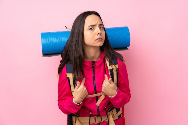 Młoda alpinista dziewczyna z dużym plecakiem nad odosobnioną menchii ścianą wskazuje do siebie