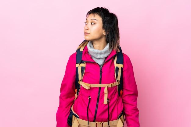 Młoda alpinista dziewczyna z dużym plecakiem nad odosobnioną różową przyglądającą stroną