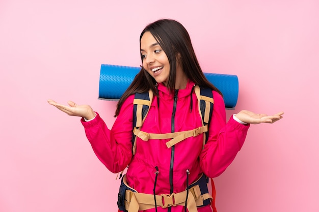 Młoda alpinista kobieta z dużym plecaka mienia copyspace z dwoma rękami