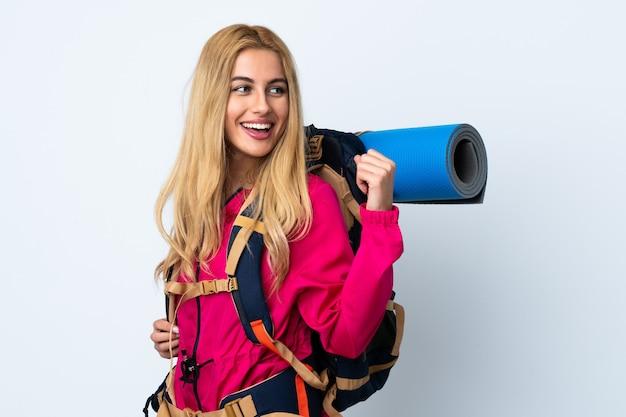 Młoda alpinista kobieta z dużym plecakiem nad odosobnioną biel ścianą