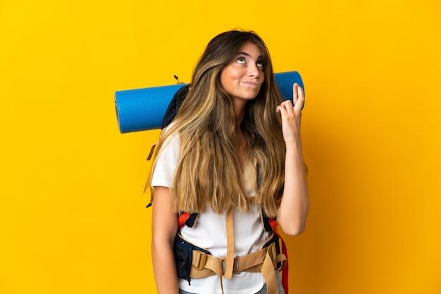 Młoda alpinistka kobieta z dużym plecakiem na białym tle na żółto z palcami krzyżującymi i życzącymi wszystkiego najlepszego