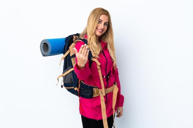 Młoda alpinistka kobieta z dużym plecakiem nad odosobnioną biel ścianą zaprasza przyjeżdżać