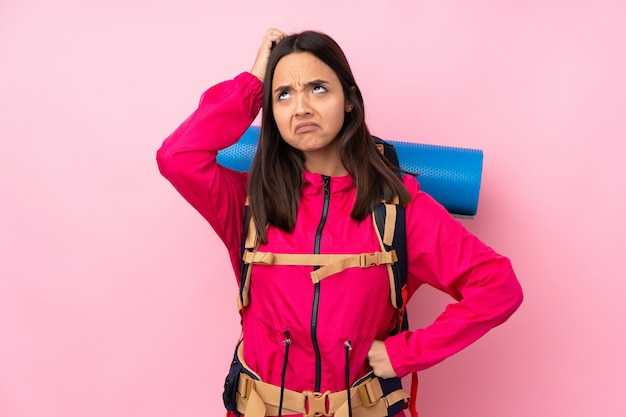 Młoda alpinistka z dużym plecakiem mającym wątpliwości podczas drapania głowy