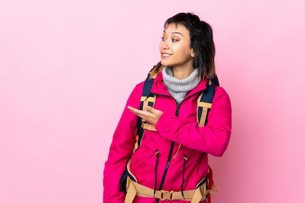 Młoda alpinistka z dużym plecakiem na białym tle różowy, wyciągając ręce na bok za zaproszenie