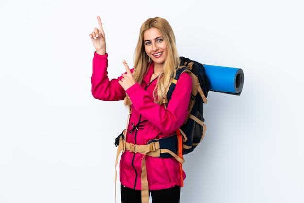 Młoda alpinistka z dużym plecakiem na białym tle wskazującym palcem wskazującym świetny pomysł