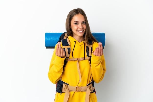 Młoda alpinistka z dużym plecakiem na odosobnionym białym tle robi gest pieniędzy