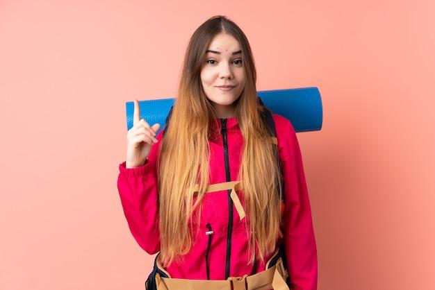 Młoda alpinistka z dużym plecakiem na różowej ścianie wskazująca palcem wskazującym świetny pomysł