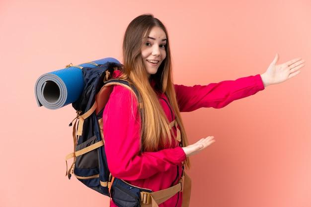 Młoda alpinistka z dużym plecakiem na różowej ścianie wyciągającej ręce z boku za zaproszenie