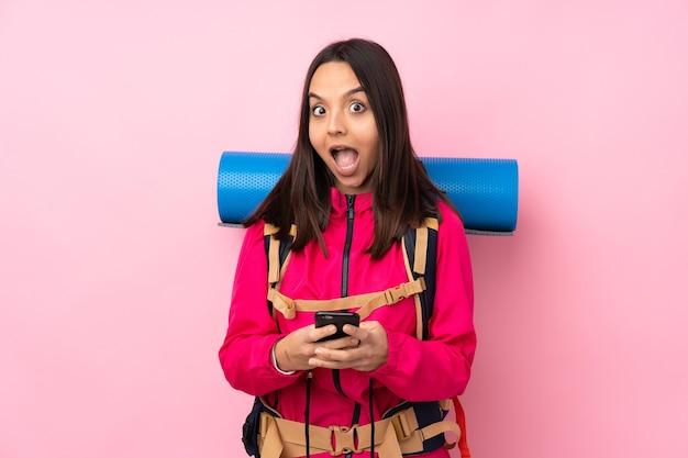 Młoda alpinistka z dużym plecakiem na różowym zaskoczona i wysyłająca wiadomość